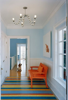 Light blue entryway by Ghislaine Vinas with a bright orange bench and striped rug