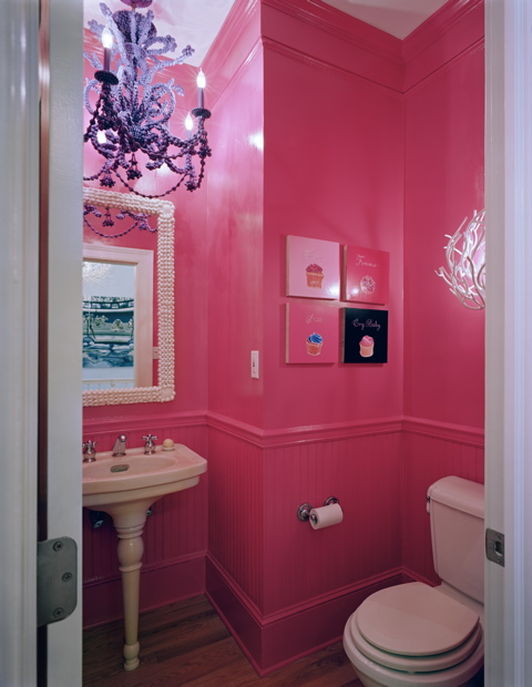 Small hot pink bathroom in a Beach House in New York by Ghislaine Vinas with mirror with a shell trim, chandelier and a pedestal sink