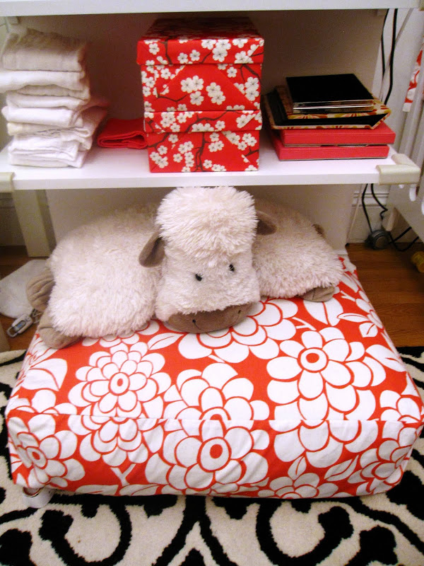 Cute white cow on a pink and white floral floor pillow in a nursery in an NYC loft with custom storage boxes