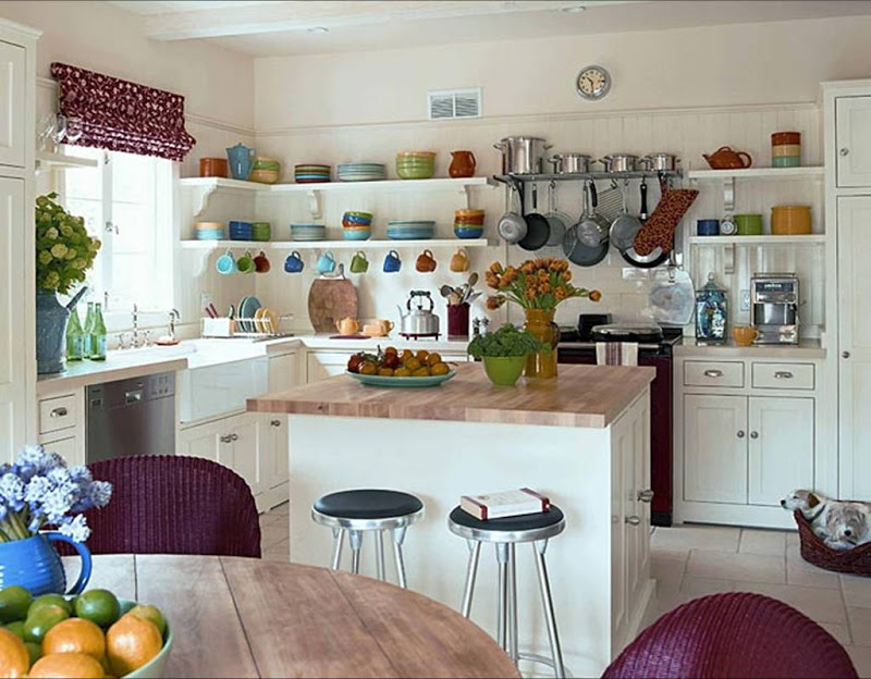Kitchen with butcher block countertops, open shelving, white cabinets and purple Roman shades and wicker dining chairs