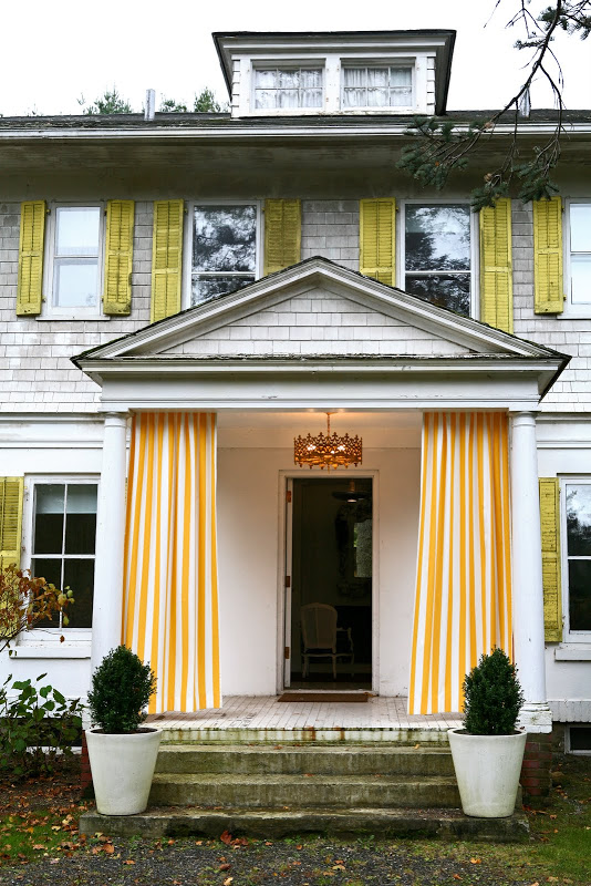 White shingled house with yellow trim and yellow and white drapery panels