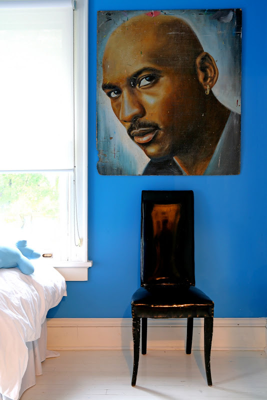 Blue bedroom by Robert and Cortney Novogratz with a black patent chair with a high back under a painting of Michael Jordan