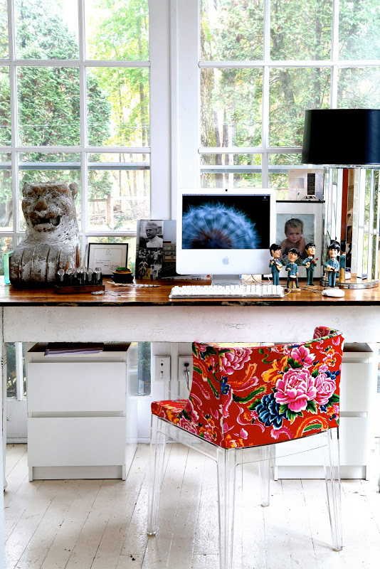 Home office by Robert and Cortney Novogratz with a  lucite Mademoiselle Kartell chair with Missoni fabric in front of a picture window