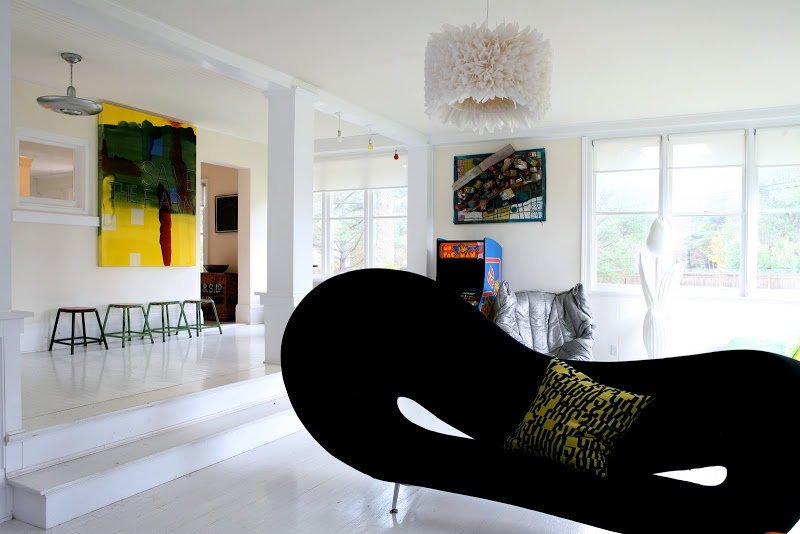 Eclectic family room by Robert and Cortney Novogratz with a bow tie shaped black sofa and a spiky chandelier