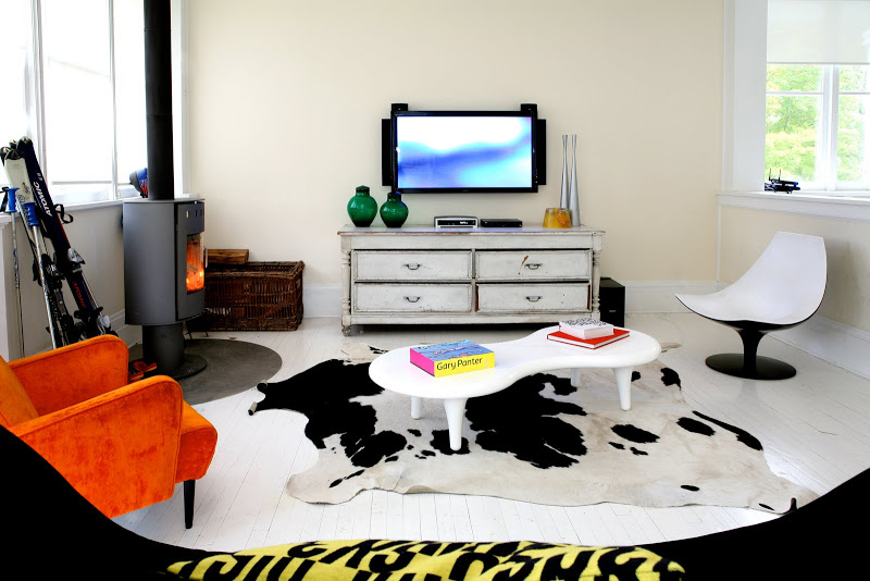 Ecletic family room by Robert and Cortney Novogratz with cow hide rug, black bow tie sofa, white modern coffee table, orange armchair and freestanding fireplace