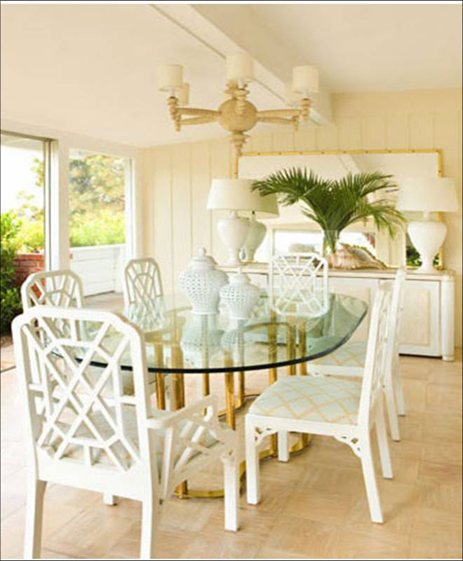 Dining room by Kristen Hutchins with glass table with a brass base surrounded by white lacquer chairs