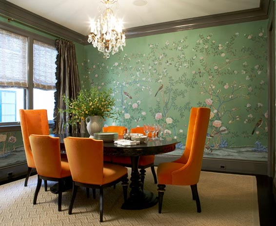 Formal dining room with green wallpaper and orange upholstered chairs