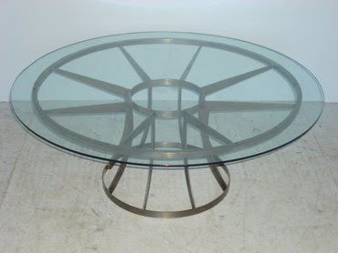 Round glass top coffee table with metal spoke base from Mecox Gardens