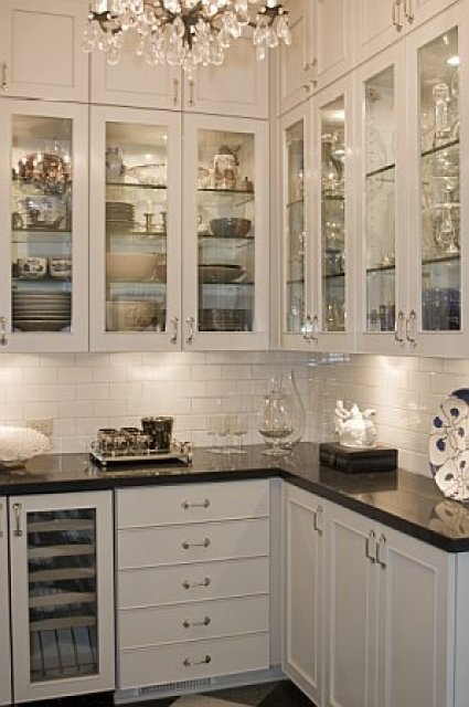 Butler pantry after remodeling by Newman & Wolen Design with crystal chandelier, under counter lights and glass upper cabinets