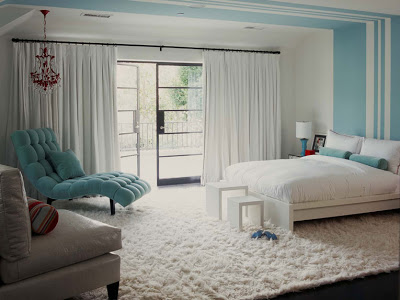 Turquoise bedroom with painted stripe headboard, tufted blue chaise lounge, bolster neck pillows and a matching side lamp