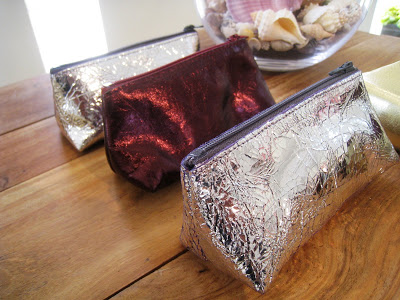 Small metallic make up cases in silver, plum and pewter from Persimmon