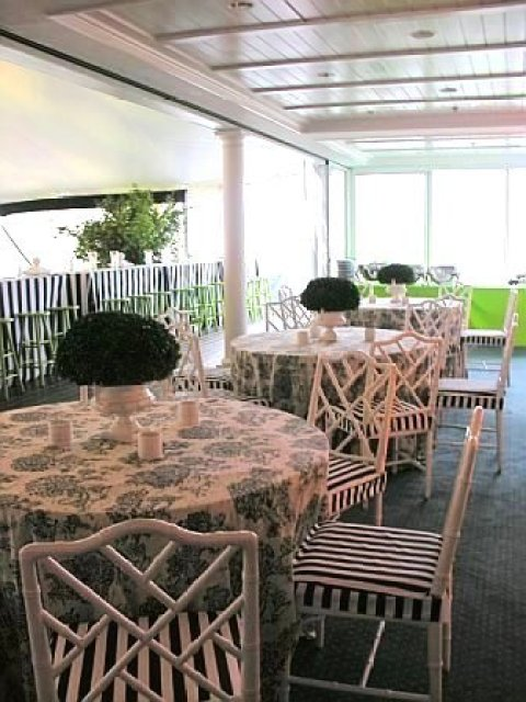 Dining tables at a wedding designed by Delaney Todd Bagwell with black and white tolie tablecloths, white Chippendale chairs with black and white striped seat cushions and green centerpieces