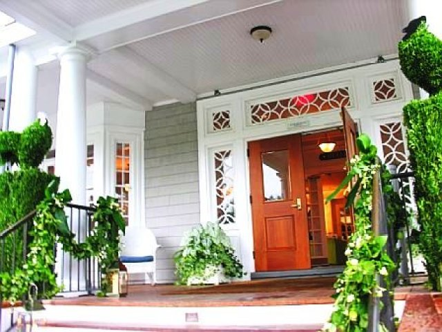 Exterior of a club prepared for a wedding with green garlands on the stair railing and poultry inspired topiaries by Delaney Todd Bagwell