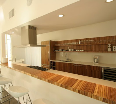 Bright open kitchen with modern amenities like exotic wood cabinets, bar counter and integrated appliances after The Sunset Team/La Kaza Design's remodeling