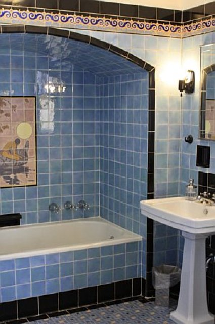 Guest bathroom with blue and black tiles and a white pedestal sink