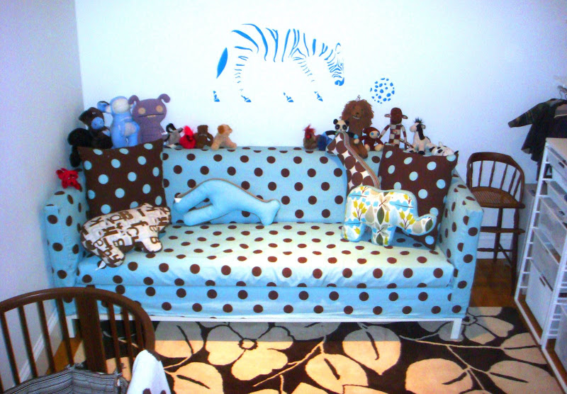 Blue and white polka dot Jonathan Adler Lampert Sofa in a nursery with lots toys and pillows