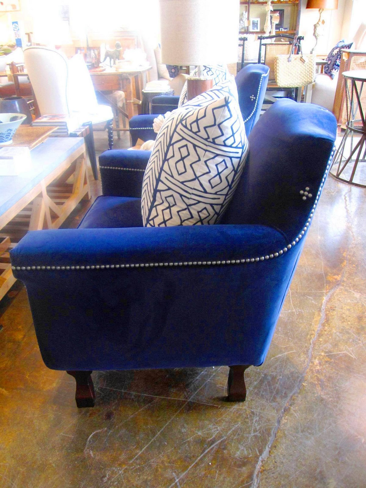 side view of a dark blue velvet armchair with wood legs and pewter nailhead trim from - Blue Velvet Chair