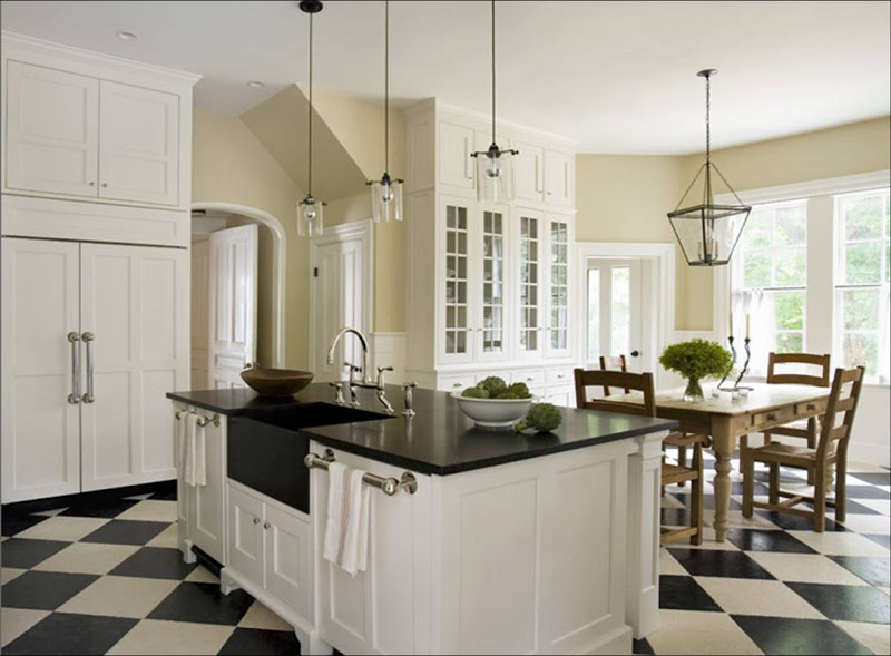 Kitchen with black and white checkerboard tile floor, glass upper cabinets, a wood farmhouse style table and metal lanterns