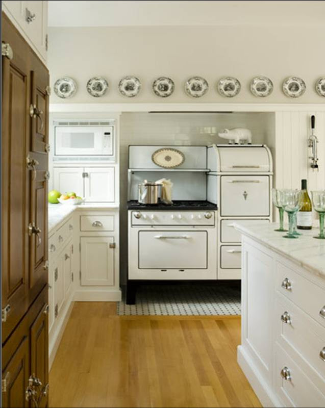 Vintage inspired kitchen with vintage stove and oven set, decorative plates on floating shelves and white drawers and cabinetry