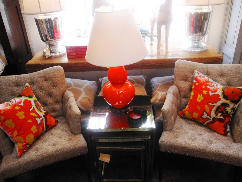 Two tufted twee armchairs with nailhead trim and a nesting table with gold metal base and antique mirror top at Mecox Garden with bright accent pillows and table lamp
