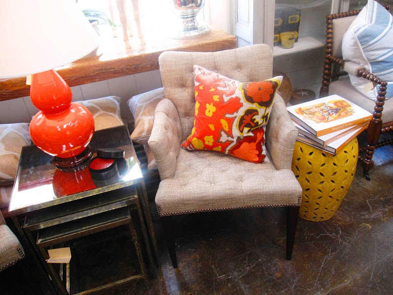 Tufted tweed armchair and a nesting table with an antique mirrored top at Mecox Garden with bright accent pillows and table lamp