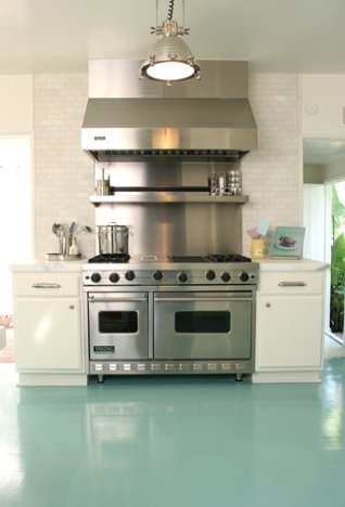 Beach house kitchen with turquoise high gloss painted wood floor, stainless appliances, nickle pendant light and a white subway tile backsplash
