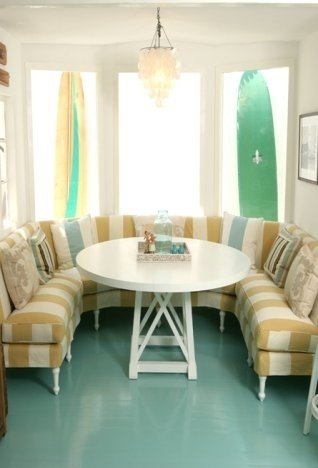 Breakfast nook with turquoise high gloss painted wood floor, two surfboards as decoration and yellow and white stripped banquette seating