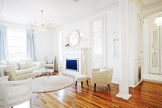"""White living room by Kelly Giesen with rolled slipcovered sofa, shag rug, cane back chair, wingback chair, lucite table and mid century vintage barrel armchair, columns and a TV inside the """"fireplace"""""""