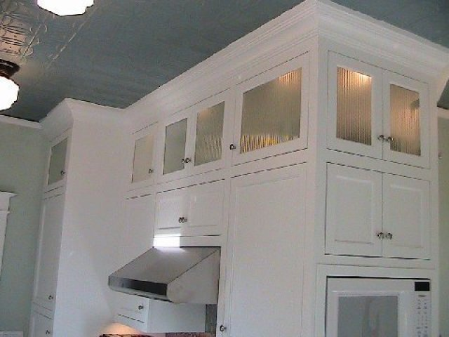 Kitchen after remodeling with white upper cabinets with reeded glass fronts and accent lights
