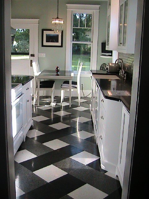 Renovated kitchen with grey black and white tile floor nad mint walls inspired by Tom Newman