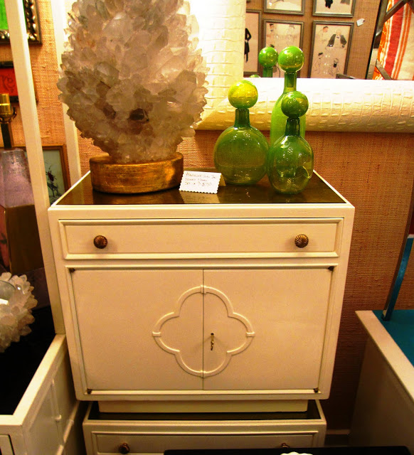 White lacquer side table with a lucite and gold told inside the Elizabeth Bauer store