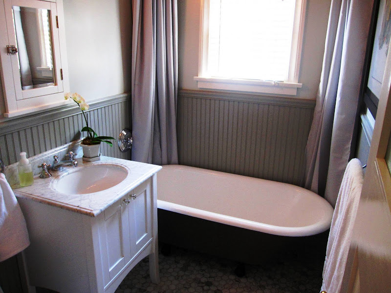 Grey bathroom by Newman & Wolen Design with black freestanding tub, grey beadboard wainscoting and marble countertops