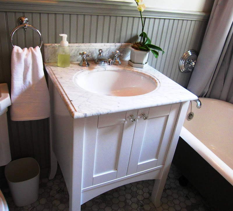 White wood vanity cabinet in a bathroom by Newman & Wolen Design with hexagon marble mosaic tile floor, claw foot tub and grey wainscoting