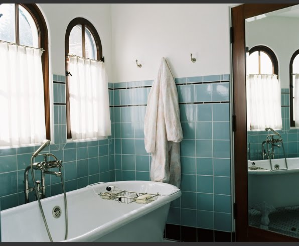 Los Angeles area bathroom with square ceramic tiles in blue and black trim and base molding, a freestanding tub, arched windows and a mirrored door