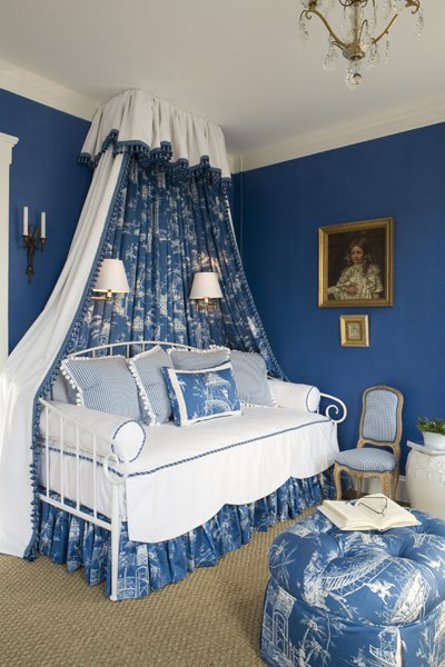 Bedroom by Kelley Proxmire with a white iron day bed, a blue and white Chinoisserie toile valance canopy with matching bed skirt and tufted ottoman