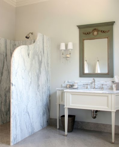 French bathroom with trumeau style mirror and a curved marble slab shower screen
