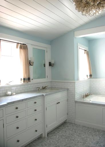 Bathroom by Kevin Oreck with vaulted white wood plank ceiling, capiz shell Chandelier, light blue walls and hexagon mosaic tile floor