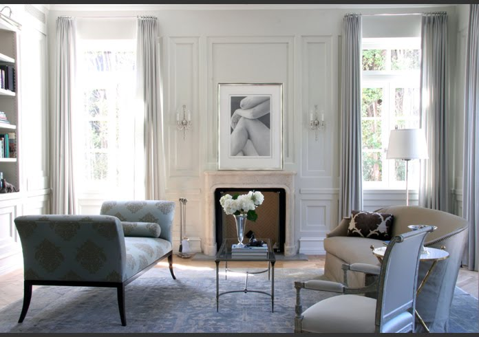 Traditional living room by William Hefner with high ceiling, grey paneled walls, a stone fireplace mantel, tall windows