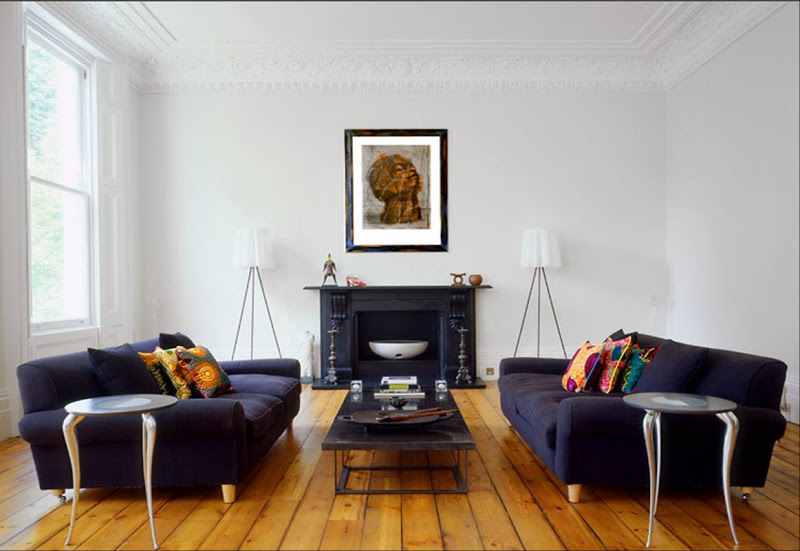 Modern living room with crown moldings, dueling dark blue sofas, wide plank wood floor and a black fireplace mantel