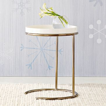 Side table with a round top with removable lacquer wood tray on polished bronze base from West Elm