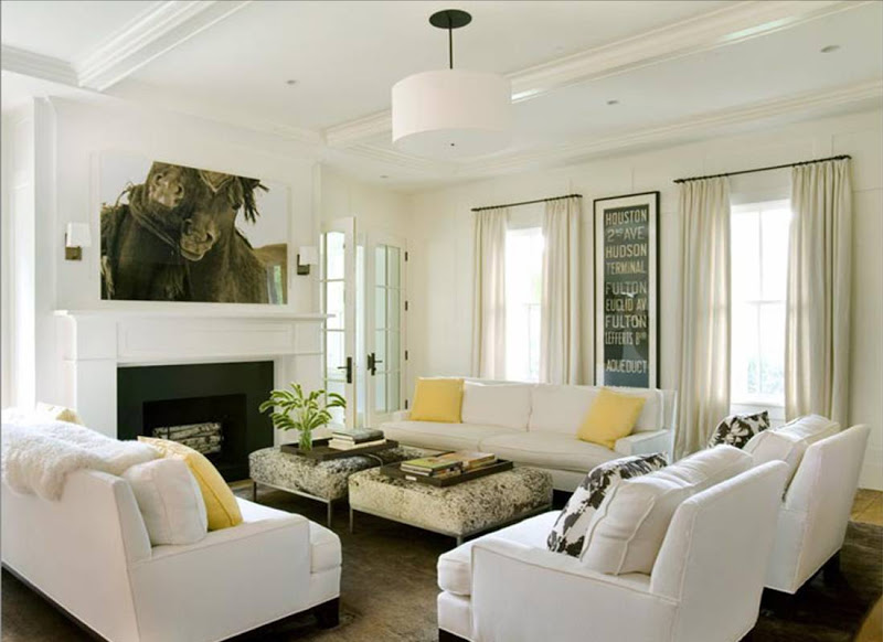 White living room with coffered ceiling, dueling sofas with yellow accent pillows and a white drum pendant light