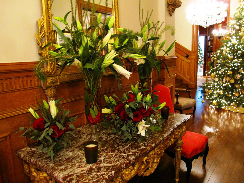 Main entry hall in a historic New Orleans mansion with a flower arrangement of white star gazer lilies, pine tree branches, eucalyptus leaves, red berries and a touch of red food coloring