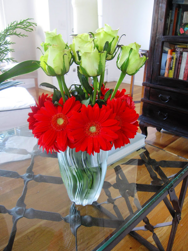 Flower arrangement with red Gerber daisies and green roses