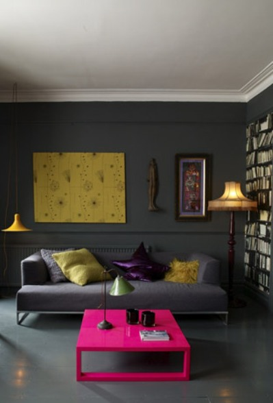 Dark grey living room with grey floor, built in bookshelf, grey sofa, a yellow lamp and a hot pink coffee table