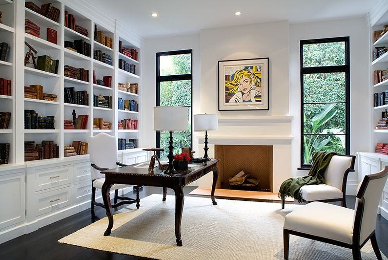 Home office in a Spanish revival home with white built in bookshelf, traditional wood desk and wood chairs with white seats and backs, a fireplace with a a Roy Lichtenstein print on the mantel and black paned windows