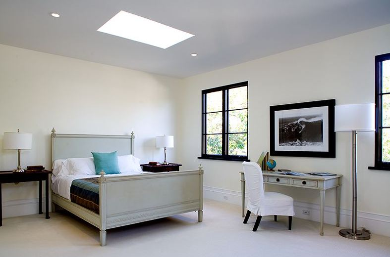 Bedroom in a Spanish Revival home with black paned windows, a skylights and matching grey bed frame and desk