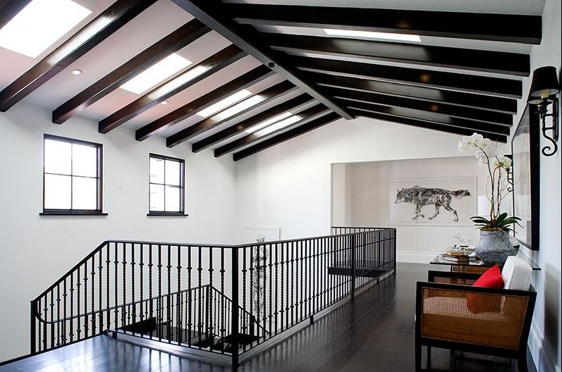Second floor hallway in a Spanish Revival home with exposed painted black beams