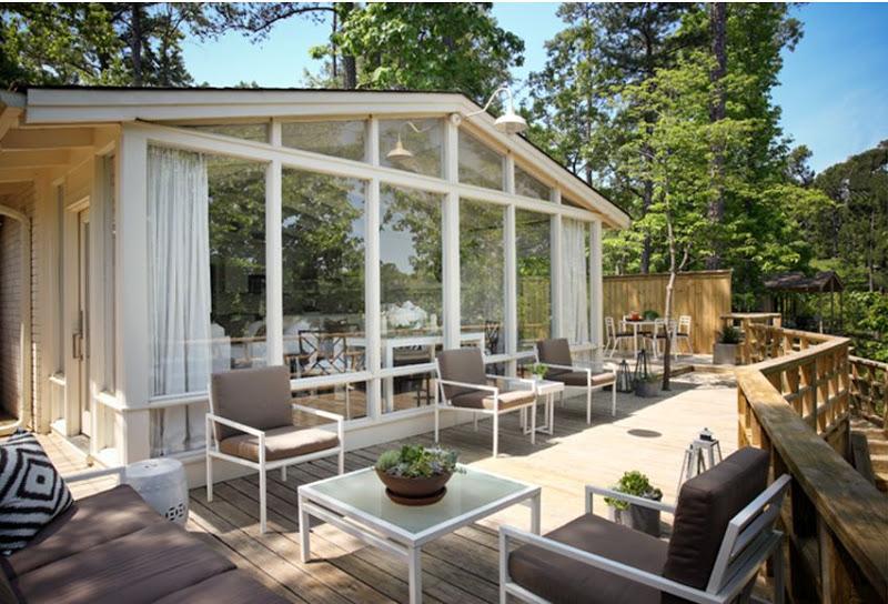 Outdoor patio with white iron furniture, diamond ikat style pillows, white ceramic garden stools and a lake view