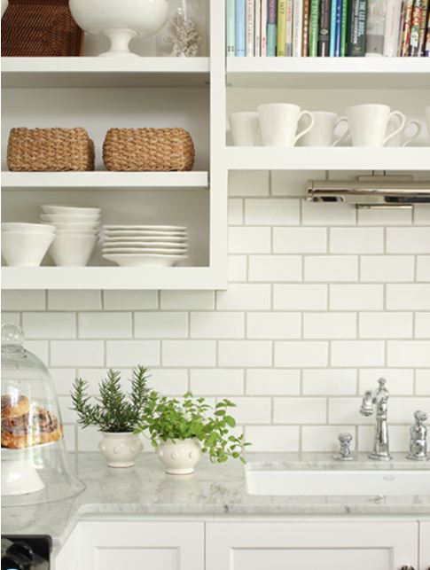 Close up of the kitchen with white subway tile backplash and carrara marble counter