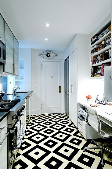 Kitchen with diamond patterned black and white tile floor, white cabinets and a built in desk